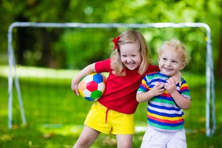 preescolar: Dos niños felices jugando fútbol europeo al aire libre en el patio de la escuela. Los niños juegan al fútbol. Deporte activo para el niño preescolar. Juego de bola para el joven equipo chico. Niño y niña marcar un gol en el partido de fútbol. Foto de archivo