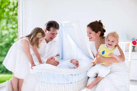 白い寝室で 4 人の子供を持つ大家族。親と子供が生まれたばかりの赤ちゃんの男の子のまぐさ桶に立っています。母とモーゼ バスケットで生まれた 写真素材