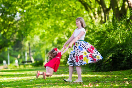 columpios: Familia con niños jugando en un parque. Mujer y pequeño giro niña y la danza en el jardín. Abuela y nieta juegan al aire libre. Vestido de verano para la madre y su hija. Padres activos con niños.