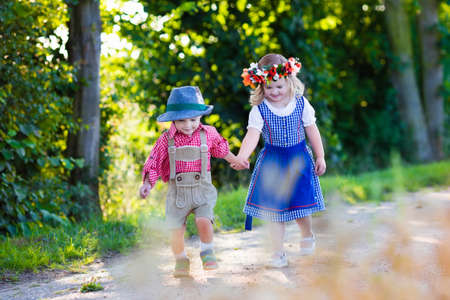 harvest festival: Kids in traditional Bavarian costumes in wheat field. German children eating bread and pretzel during Oktoberfest in Munich. Brother and sister play outdoors during autumn harvest time in Germany.