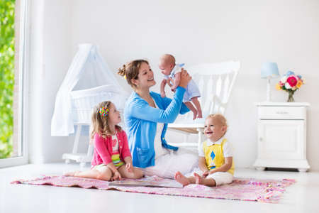 Mother and children play indoors. Family with kids in a white bedroom. Mom with baby, boy and girl playing and reading books at home. Beautiful nursery for baby and toddler. Room for preschool child. Banco de Imagens
