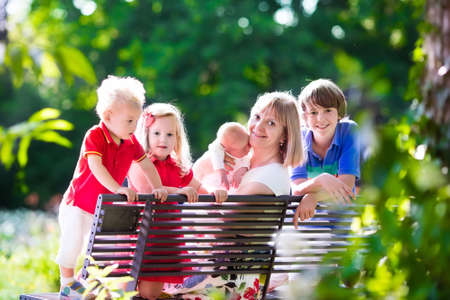 mother on bench: Big family with kids playing in a park. Woman and children relax on a bench in the garden. Grandmother and grandchildren play outdoors in summer. Mother with baby, toddler, preschooler and teenager.