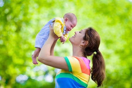 recien nacido: Madre que celebra al beb� reci�n nacido en un parque. Mama que juega con su hijo reci�n nacido en el jard�n. Familia con ni�os jugar al aire libre. Mujer joven que abraza ni�o. Los padres y los ni�os se divierten en el verano.