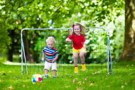 niños jugando en la escuela: Dos niños felices jugando fútbol europeo al aire libre en el patio de la escuela. Los niños juegan al fútbol. Deporte activo para el niño preescolar. Juego de bola para el joven equipo chico. Niño y niña marcar un gol en el partido de fútbol. Foto de archivo