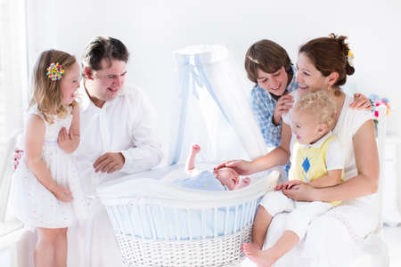 twin sister: Big family with four kids in white bedroom. Parents and kids standing at crib of newborn baby boy. Mother and playing with new born child in moses basket. Kids meeting new sibling. Nursery for infant. Stock Photo
