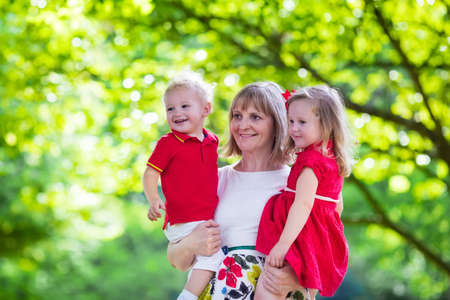 grandmother and children: Mother and children play in a park. Woman holding little toddler daughter and son. Siblings with little age difference. Boy and girl twins. Young grandmother with grandchildren in sunny summer garden. Stock Photo