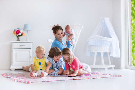 Mother and children play indoors. Family with kids in a white bedroom. Mom with baby, boy and girl playing and reading books at home. Beautiful nursery for baby and toddler. Room for preschool child. Banque d'images