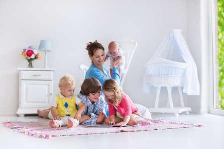 spielende kinder: Mutter und Kinder spielen im Freien. Familie mit Kindern in einem weißen Schlafzimmer. Mutter mit Kind, Junge und Mädchen spielen und Bücher lesen zu Hause. Schöne Kindergarten für Baby und Kleinkind. Platz für Kind im Vorschulalter.