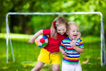 niños jugando: Dos niños felices jugando fútbol europeo al aire libre en el patio de la escuela. Los niños juegan al fútbol. Deporte activo para el niño preescolar. Juego de bola para el joven equipo chico. Niño y niña marcar un gol en el partido de fútbol. Foto de archivo