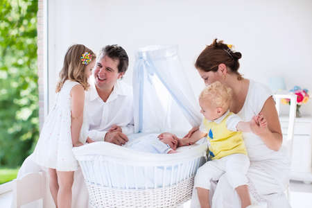 for kids: Big family with four kids in white bedroom. Parents and kids standing at crib of newborn baby boy. Mother and playing with new born child in moses basket. Kids meeting new sibling. Nursery for infant. Stock Photo