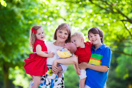 grand sons: Mother and children play in a park. Woman with newborn baby, little girl, toddler and teenager boy. Siblings with big age difference. Kids with large age gap. Young grandmother with grandchildren.