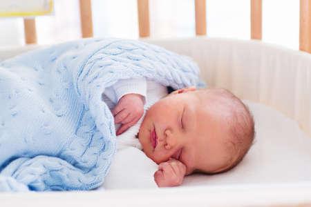Nyfött barn på sjukhus rum. Nyfödda barn i trä co-sleeper krubba. Spädbarn sover i sängen korg. Säker samsovning i en säng sida barnsäng. Liten pojke tar en tupplur under stickad filt.