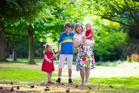 grand kid: Grandmother and grandchildren enjoying picnic in a park. Grandma playing with children in a sunny autumn forest. Summer outdoor fun in the garden. Grandparents and kids on a meadow. Stock Photo