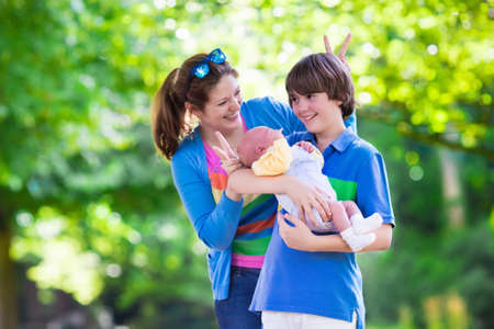 new age: Mother and children play in a park. Young mom with two sons, newborn and teenager boy. Siblings with big age difference. Brothers with large age gap. Teen kid holding new baby. Parents and kids fun.