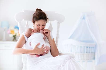 Jonge moeder die haar pasgeboren kind. Moeder zogende baby. Vrouw en pasgeboren jongen ontspannen in een witte kamer met schommelstoel en blauwe wieg. Kwekerij interieur. Moeder borstvoeding baby. Familie thuis Stockfoto