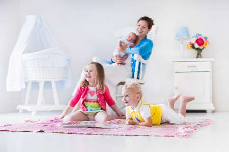 Mother and children play indoors. Family with kids in a white bedroom. Mom with baby, boy and girl playing and reading books at home. Beautiful nursery for baby and toddler. Room for preschool child. Stock Photo