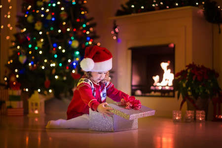 xmas presents: Family on Christmas eve at fireplace. Kids opening Xmas presents. Children under Christmas tree with gift boxes. Decorated living room with traditional fire place. Cozy warm winter evening at home. Stock Photo