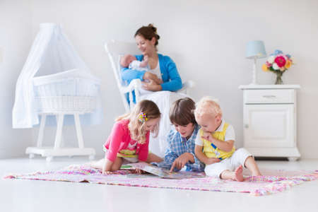 for kids: Mother and children play indoors. Family with kids in a white bedroom. Mom with baby, boy and girl playing and reading books at home. Beautiful nursery for baby and toddler. Room for preschool child. Stock Photo