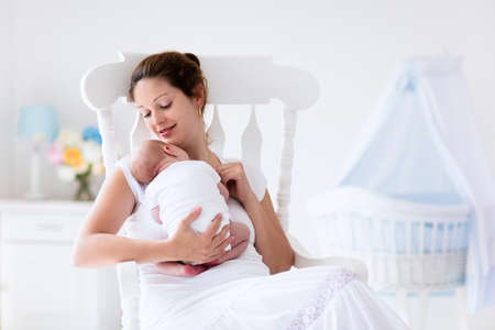 child girl nude: Young mother holding her newborn child. Mom nursing baby. Woman and new born boy relax in a white bedroom with rocking chair and blue crib. Nursery interior. Mother breast feeding baby. Family at home