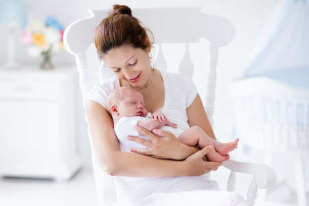 beaux seins: Jeune mère tenant son enfant nouveau-né. Soins infirmiers maman bébé. Femme et le nouveau garçon né détendre dans une chambre blanche avec chaise berçante et berceau bleu. Nursery intérieur. Mère bébé de l'allaitement maternel. Famille à la maison