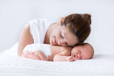 Young mother hugging her newborn child. Mom nursing baby. Woman and new born boy relax in a white bedroom. Family at home. Love, trust and tenderness concept. Bedding and textile for nursery. 免版税图像