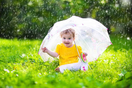 outdoor outside: Little girl with colorful umbrella playing in the rain. Kids play outdoors by rainy weather in fall. Autumn outdoor fun for children. Toddler kid outside in the garden. Baby enjoying summer shower.