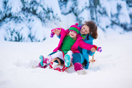 outdoors: Young mother and little girl enjoying sleigh ride. Child sledding. Toddler kid riding sledge. Children play outdoors in snow. Kids sled in snowy park. Outdoor winter fun for family Christmas vacation.