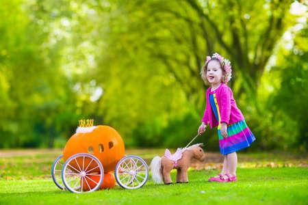 Cute bambina riccia giocando Cenerentola fiaba tiene la bacchetta magica accanto a una carrozza zucca in autunno parco a Halloween. Bambini trick or treat in campo di zucche. Famiglia con figli carving. Archivio Fotografico