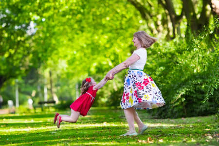 swings: Family with kids playing in a park. Woman and little girl spin and dance in the garden. Grandmother and granddaughter play outdoors. Summer dress for mother and daughter. Active parents with children. Stock Photo