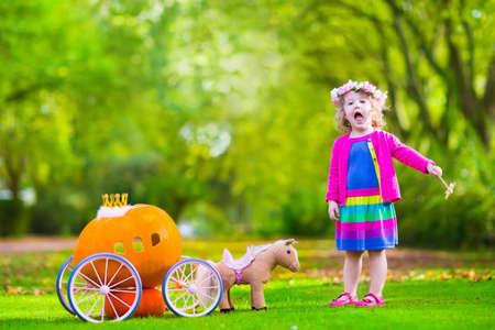 Cute bambina riccia giocando Cenerentola fiaba tiene la bacchetta magica accanto a una carrozza zucca in autunno parco a Halloween. Bambini trick or treat in campo di zucche. Famiglia con figli carving.