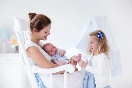 Little sister hugging her newborn brother. Toddler kid meeting new sibling. Mother and new born baby boy relax in a white bedroom. Family with children at home. Love, trust and tenderness concept.