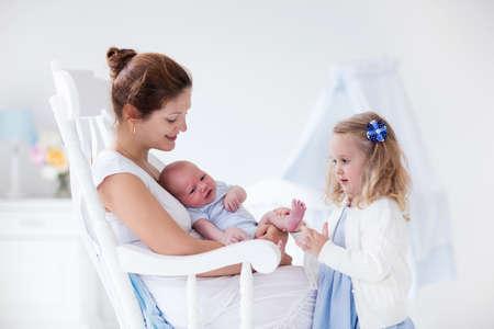 Zusje knuffelen haar pasgeboren broertje. Peuter jongen ontmoeten van nieuwe broer of zus. Moeder en pasgeboren baby jongen ontspannen in een witte kamer. Gezin met kinderen thuis. Liefde, vertrouwen en tederheid concept.