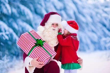 niños ayudando: Santa Claus y los niños que abren presentes en el bosque cubierto de nieve. Los niños y el padre en el traje de Santa y barba abierta regalos de Navidad. Niña que ayuda con el actual saco. Navidad, la nieve y el invierno de la diversión para la familia. Foto de archivo
