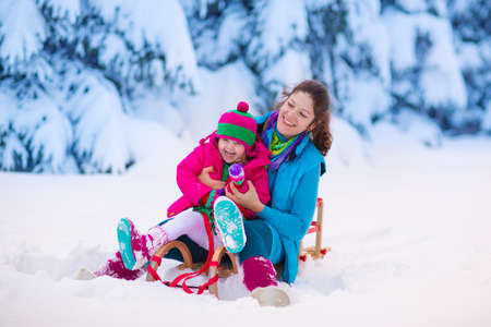 winter sports: Young mother and little girl enjoying sleigh ride. Child sledding. Toddler kid riding sledge. Children play outdoors in snow. Kids sled in snowy park. Outdoor winter fun for family Christmas vacation.