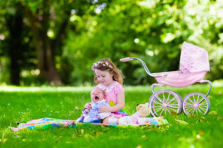 Family with children enjoying picnic outdoors. Little girl playing with newborn baby brother in summer park. Child playing with toy stroller. Sister kissing new born sibling. Kids birthday party. Stock Photo