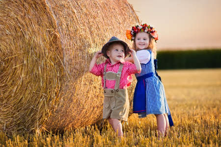 harvest: Kids in traditional Bavarian costumes in wheat field. German children eating bread and pretzel during Oktoberfest in Munich. Brother and sister play at hay bales during autumn harvest time in Germany