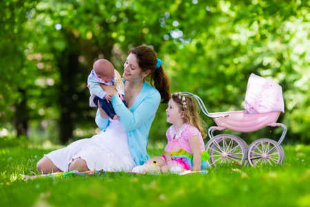 childrens birthday party: Family with children enjoying picnic outdoors. Mother with newborn baby and toddler child relax in a park. Little girl playing with toy stroller. Mom and kid play with infant boy. Kids birthday party.
