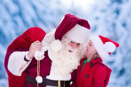 дети: Дед Мороз и дети открытия подарки в заснеженном лесу. Дети и отец в костюме Санта и борода открыт рождественских подарков. Маленькая девочка, помогая с настоящим мешок. Рождество, снег и зимние развлечения для семьи. Фото со стока