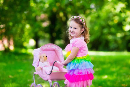 children at play: Little girl pushing toy stroller with bear. Toddler kid in pink dress playing with doll buggy. Kids birthday party. Children play outdoors. Mother and baby role game. Family summer fun. Preschool toys Stock Photo