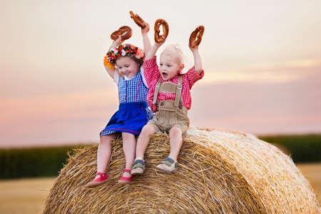 comiendo pan: Niños en trajes bávaros tradicionales en campo de trigo. Niños alemanes comen pan y pretzel durante la Oktoberfest en Munich. Hermano y hermana en juego las balas de heno durante el tiempo de la cosecha de otoño en Alemania