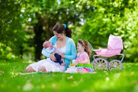 ni�os caminando: Familia con ni�os disfrutando de picnic al aire libre. Madre con el beb� reci�n nacido y el ni�o ni�o a relajarse en un parque. Ni�a que juega con el cochecito de juguete. Mam� e hijo juegan con el ni�o reci�n nacido. Ni�os fiesta de cumplea�os.
