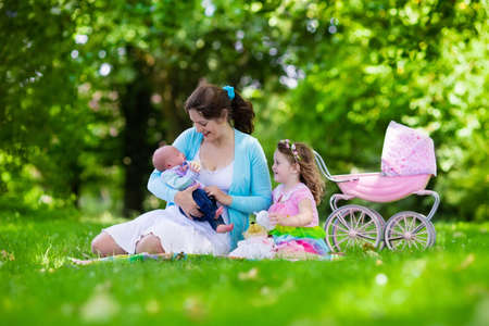 baby doll: Family with children enjoying picnic outdoors. Mother with newborn baby and toddler child relax in a park. Little girl playing with toy stroller. Mom and kid play with infant boy. Kids birthday party.