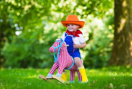 bandana western: Little boy dressed up as cowboy playing with his toy rocking horse in a summer park. Kids play outdoors. Children in Halloween costumes at trick or treat. Toys for preschooler or toddler child. Stock Photo