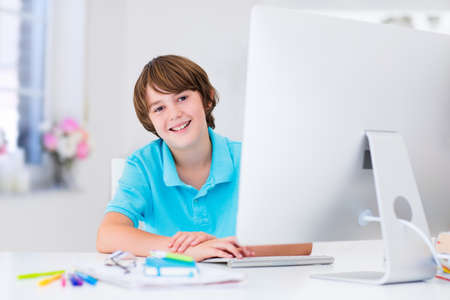study: School boy working on personal computer at home. Student doing homework using modern pc in classroom. Kids studying with digital devices. Children study in white class room. Child learning.