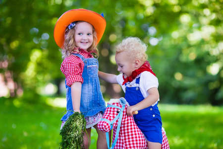 Little boy and girl dressed up as cowboy and cowgirl playing with toy rocking horse in park. Kids play outdoors. Children in Halloween costumes at trick or treat. Toys for preschooler or toddler child Stock Photo