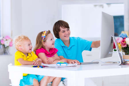 learning by doing: School kids working on personal computer at home. Student doing homework using modern pc in classroom. Kids studying with digital devices. Children study in white class room. Child learning. Stock Photo