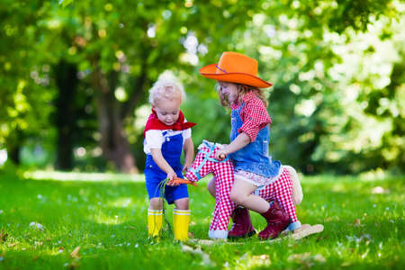 wild west: Little boy and girl dressed up as cowboy and cowgirl playing with toy rocking horse in park. Kids play outdoors. Children in Halloween costumes at trick or treat. Toys for preschooler or toddler child Stock Photo