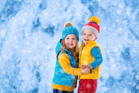 toddler boy: Little girl and boy in yellow and blue knitted hat catching snowflakes in winter park on Christmas eve. Kids play outdoor in snowy winter forest. Children catch snow flake on Xmas. Toddler kid playing