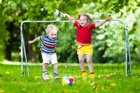 kids club: Two happy children playing European football outdoors in school yard. Kids play soccer. Active sport for preschool child. Ball game for young kid team. Boy and girl score a goal in football match.