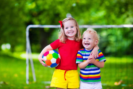 Two happy children playing European football outdoors in school yard. Kids play soccer. Active sport for preschool child. Ball game for young kid team. Boy and girl score a goal in football match.